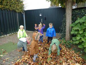 foto van kinderen die met bladeren spelen in de herfst